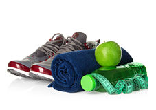 Fitness, weight loss concept with sneakers, green apples, bottle of drinking water and tape measure Royalty Free Stock Photos