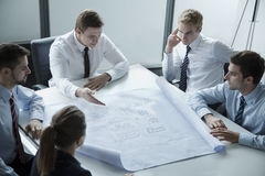 Five architects discussing and planning over a blueprint in the office Stock Photography