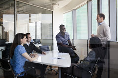 Five business people sitting at a conference table and discussing during a business meeting Stock Photo