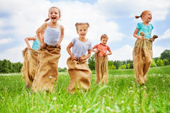 Five kids jump in sacks Royalty Free Stock Photography