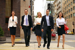 Five successful business people crossing the street in the city Stock Photo
