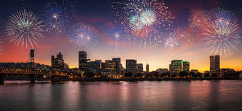 Flashing fireworks on a dramatic sunset sky with Portland, OR cityscape with Willamette river Stock Image