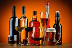 Flaskor och exponeringsglas av alkoholdrinkar Arkivfoto