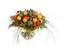 Floral composition of orange roses, hypericum and fern. Flower arrangement in a transparent glass vase. Isolated on white. Royalty Free Stock Photography