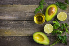 Food background with fresh organic avocado, lime, parsley and ol Royalty Free Stock Photos