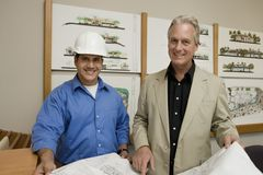Foreman With Client Holding Blueprint Royalty Free Stock Image