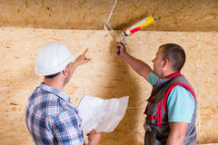 Foreman Instructing Worker How to Apply Caulk Royalty Free Stock Photos