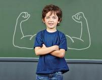 Forte bambino con i muscoli a scuola Fotografie Stock