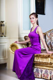 Frau im purpurroten Kleid im Luxusinnenraum Stockfotos