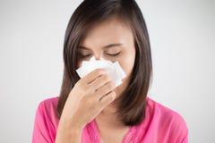 Freddo di influenza o sintomo di allergia Ragazza malata della donna che starnutisce nel tessuto Fotografie Stock