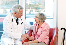 Friendly doctor reassuring an elderly woman. Royalty Free Stock Images