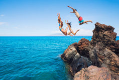 Friends cliff jumping into the ocean Stock Photos