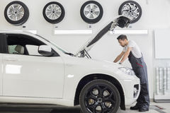Full length side view of male mechanic examining car engine in repair shop Royalty Free Stock Image