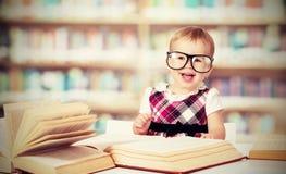 Funny baby girl in glasses reading book in library Stock Photo