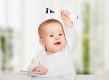 Funny baby with a knife and fork eating food Royalty Free Stock Photos