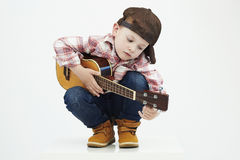 Funny child boy with guitar.ukulele guitar. fashionable country boy playing music Stock Photography