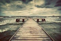 Gammal träbrygga under storm på havet Dramatisk himmel med mörker, skurkrollmoln Arkivbild