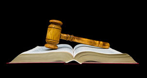 Gavel lies on the open book. black background. Stock Photos