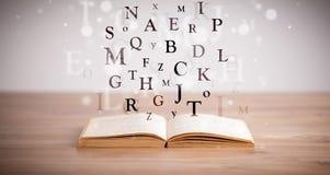 Geöffnetes Buch mit Fliegenbuchstaben Stockbilder