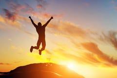 Gelukkige mens die voor vreugde op de piek van de berg bij zonsondergang springen Succes Royalty-vrije Stock Foto's