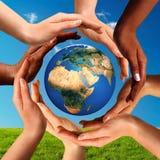 Gemischtrassige Hände zusammen um Weltkugel Lizenzfreies Stockbild