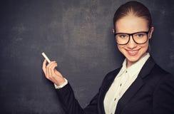 Geschäftslehrerin mit Gläsern und eine Klage mit Kreide   an a Stockbilder