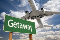 Getaway Green Road Sign and Airplane Above Royalty Free Stock Photography