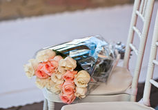 Gift rose bouquet in plastic wrapper on chair on wedding carpet Royalty Free Stock Image
