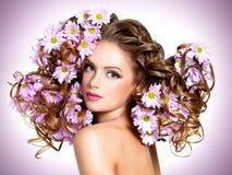 Giovane bella donna con i fiori in capelli Fotografie Stock