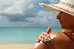 Girl aplying  sun protection cream Stock Photos