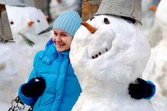Girl embraces a cheerful snowball Stock Photos