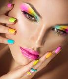 Girl face with vivid makeup and colorful nail polish Royalty Free Stock Images