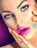 Girl face with vivid makeup and colorful nail polish Royalty Free Stock Photography