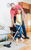 Girl helping father to do clean-up Stock Image