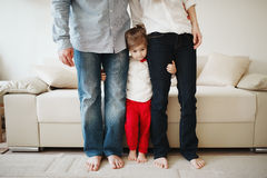 Girl hugging mom and dad for legs Stock Photography