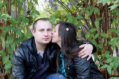 Girl kissing boy on the cheek Stock Photography