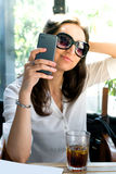 Girl looking at her smartphone and taking a selfie with glasses - telecommunication advertising Royalty Free Stock Image