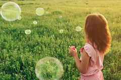Girl in pink dress blowing soap bubbles in summer Stock Image