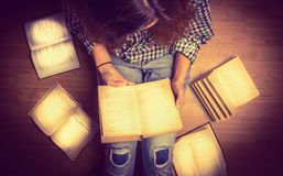 Girl in a shirt holding a book sitting on the floor around her spread open books close up  retro  toning Stock Photo