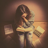 A girl sits on the floor and reading a book straightens hair with her hand close up retro  toning Stock Image