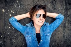 Girl with sunglasses laughing and smiling, hanging out on roof of building. Young active lifestyle people concept Royalty Free Stock Image