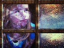 Girl at window in rain Stock Image