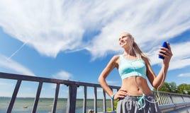 Glückliche Frau mit Smartphone und Kopfhörern draußen Stockfoto