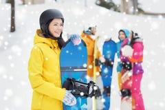 Glückliche Freunde in den Sturzhelmen mit Snowboards Stockbilder