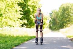 Glückliche junge Frau in den Rollerblades, die draußen reiten Stockbilder