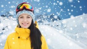 Glückliche junge Frau in den Skischutzbrillen über Bergen Lizenzfreie Stockfotografie