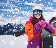 Glückliche junge Frau mit Snowboard über Bergen Lizenzfreie Stockfotografie