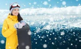 Glückliche junge Frau mit Snowboard über Bergen Lizenzfreies Stockbild