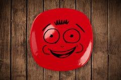 Glückliches smileykarikaturgesicht auf bunter Tellerplatte Stockbild