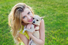 Glamour happy smiling girl or woman holding cute chihuahua puppy dog on green lawn on the sunset Royalty Free Stock Images